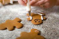 Decorating Gingerbread Men.  Christmas Cookies - the traditional gift of Christmas