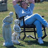 USA, Maryland,  Grett McCaleb relaxes at antique auction in farm field at Dixon's Antiques in town of Crumpton