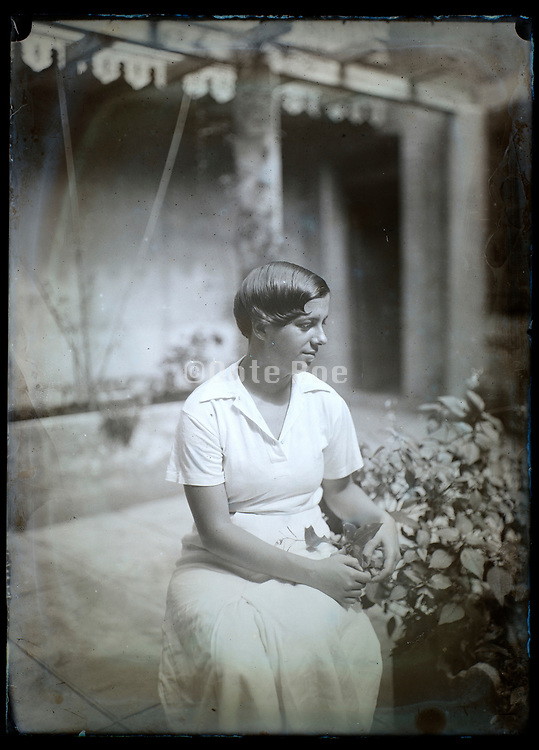 young adult woman sitting in the yard with plants France ca 1920s