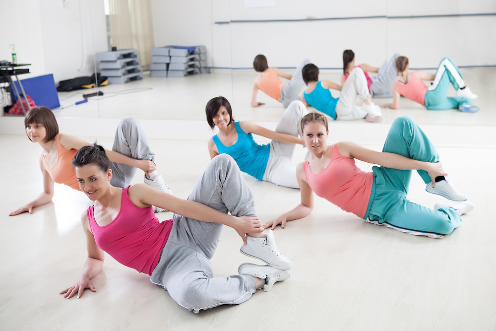 Group of smiling women exercising at a gym.