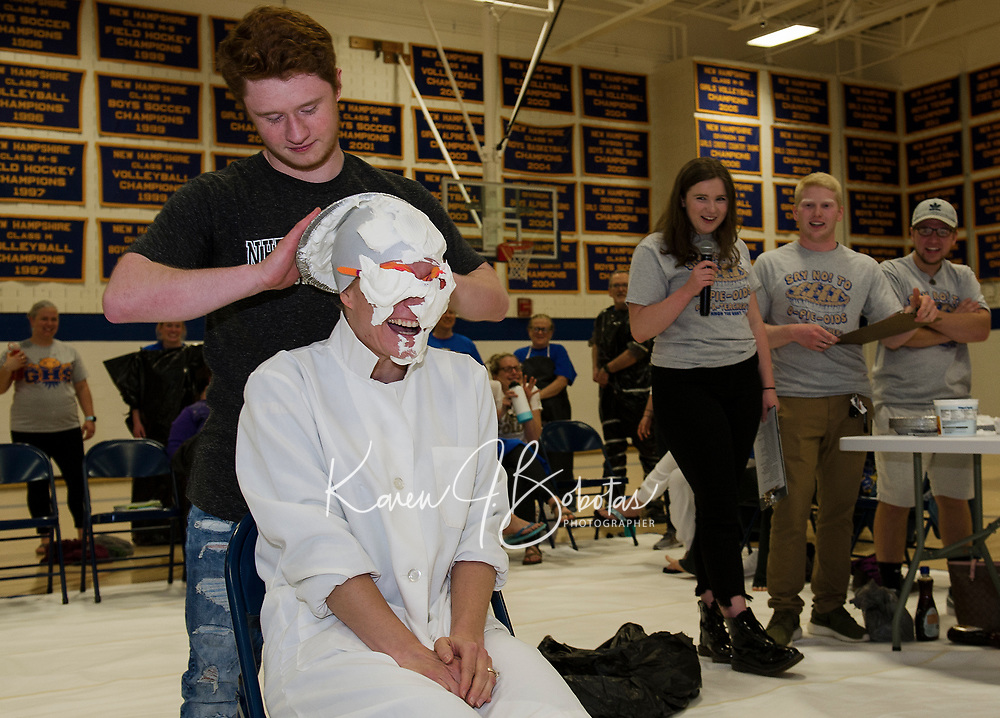 """Lorienne Valovanie came prepared as she got slathered by Ryan Hamel during Gilford High School's """"Pie a Teacher"""" to benefit The Doorway at LRGH on Friday afternoon.  (Karen Bobotas/for the Laconia Daily Sun)"""