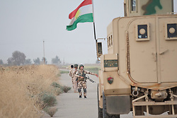 © Licensed to London News Pictures. 11/09/2015. Kirkuk, Iraq. A Kurdish peshmerga fighter, searching a road for improvised explosive devices, communicates with the crew of an armoured truck, during an offensive aimed at expanding a safety zone around Kirkuk, Iraq.<br /> <br /> The offensive, which went unchallenged after ISIS left the area ahead of the attack, saw the peshmerga capture 15 villages along the Kirkuk front line. The objective of the offensive was to expand the safety zone around Kirkuk, stopping militants from firing missiles and rockets in to the city of Kirkuk. 3 peshmerga were killed and 24 wounded due to improvised explosive devices left behind by the militants. Photo credit: Matt Cetti-Roberts/LNP