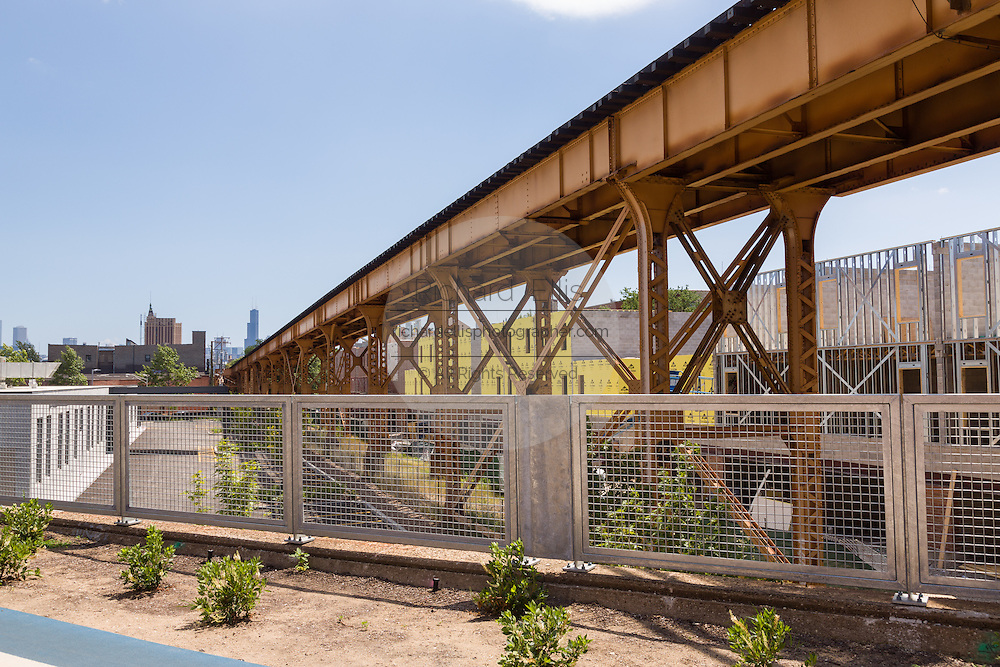 The Blue Line overpass at Milwaukee Avenue along the 606 elevated bike trail, green space and park built on the old Bloomingdale Line in the Wicker Park neighborhood in Chicago, Illinois, USA