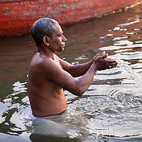 Morning rituals being performed on the banks of the holy Ganges River in Varanasi, India, at sunrise.