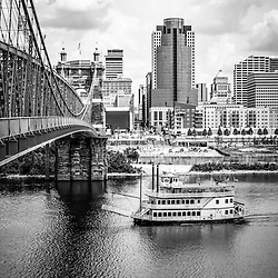 Cincinnati riverfront black and white picture with a riverboat, John Roebling Bridge, and downtown city office buildings including Omnicare building, US Bank building, and Scripps Center building. Photo Copyright © 2012 Paul Velgos with All Rights Reserved.