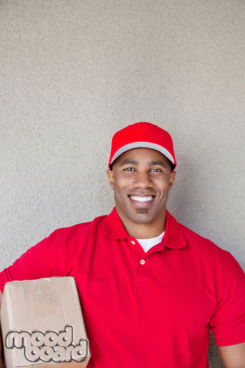 Portrait of a young man holding delivery box against wall