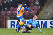 Scunthorpe United midfielder Neal Bishop (12) does sliding tackle against Shrewsbury Town striker Freddie Ladapo (19)during the EFL Sky Bet League 1 match between Scunthorpe United and Shrewsbury Town at Glanford Park, Scunthorpe, England on 11 February 2017. Photo by Ian Lyall.