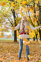 Autumn leaves falling on young woman with arms outstretched in park