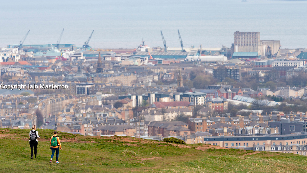 Edinburgh, Scotland, UK. 5 April, 2020. On the second Sunday of the coronavirus lockdown in the UK the public are outside taking their daily exercise. ~two women walking on  Salisbury Crags in Holyrood Park with Leith in distance. Iain Masterton/Alamy Live News