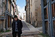 L'Aquila, Italia - 1 aprile 2013. Una veduta del centro storico dell'Aquila. Sono centinaia e centinaia i palazzi puntellati. Nella foto uno dei rari passanti che si incontrano passeggiando per le strade del centro del capoluogo abruzzese..Ph. Roberto Salomone Ag.Controluce