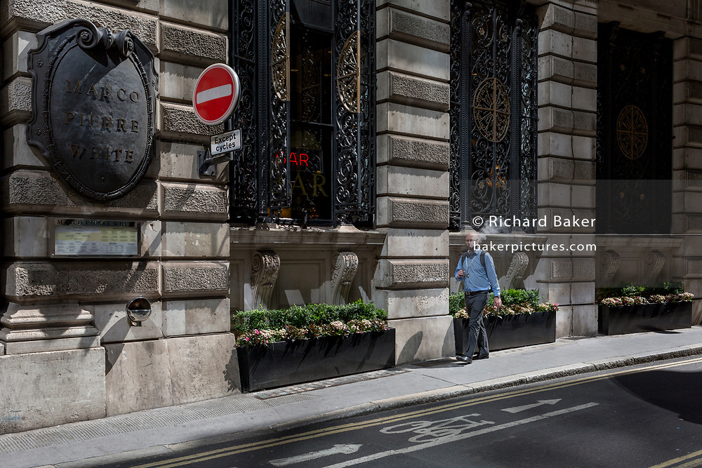 A male vaper smokes while walking along Finch Street, a narrow medieval-era lane in the City of London, the capital's historic financial district, on 2nd August 2018, in London, England.