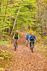 Women mountain biking on a trail on Millstone Hill in Barre, Vermont.  Abandoned granite quarry.  Fall. Millstone Trail Association.