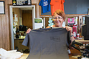 The convenience store clerk in Slapout shows the T-shirts she regularly sells to people who pass through this remote area in the Oklahoma panhandle.
