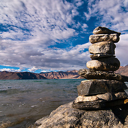 Stones are stacked like this all over Ladakh. The practice of stone stacking is sometimes seen as a form of meditation.  These stones are on the banks of Pangong Tso a lake in the Himalayas situated at a height of about 4,350 m (14,270 ft).