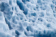 Deep blues and patterns in the ice of a large iceberg from Dawes Glacier in Endicott Arm fjord in Tracy Arm - Fords Terror Wilderness in Southeast Alaska. Inside Passage. Summer. Afternoon.