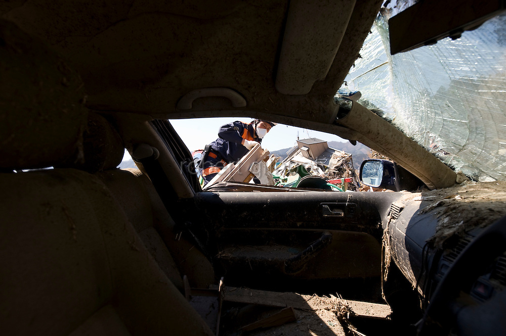 A member of the national police searches through the rubble for people still missing following the March 11 magnitude 9 quake and subsequent tsunami in Rikuzentakata on April 6, 2011..Photographer: Robert Gilhooly