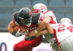 11.07.2011, UPC Arena, Graz, AUT, American Football WM 2011, Group B, Canada (CAN) vs Austria (AUT), im Bild Matt Walters (Canada, #33, RB) gets tackled by Florian Hueter (Austria, #58, LB) and Manuel Schneeweiss (Austria, #24, DB)  // during the American Football World Championship 2011 Group B game, Canada vs Austria, at UPC Arena, Graz, 2011-07-11, EXPA Pictures © 2011, PhotoCredit: EXPA/ T. Haumer