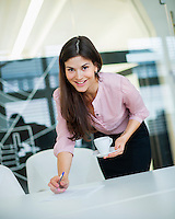 Portrait of young businesswoman holding coffee at desk in office
