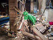 23 SEPTEMBER 2015 - BANGKOK, THAILAND: A demolition worker tears apart a home near Wat Kalayanamit. Fifty-four homes around Wat Kalayanamit, a historic Buddhist temple on the Chao Phraya River in the Thonburi section of Bangkok, are being razed and the residents evicted to make way for new development at the temple. The abbot of the temple said he was evicting the residents, who have lived on the temple grounds for generations, because their homes are unsafe and because he wants to improve the temple grounds. The evictions are a part of a Bangkok trend, especially along the Chao Phraya River and BTS light rail lines. Low income people are being evicted from their long time homes to make way for urban renewal.           PHOTO BY JACK KURTZ
