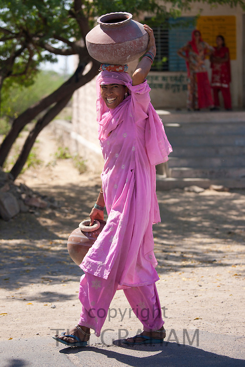 Indian woman in sari carrying water pots to fill from well at Jawali village in Rajasthan, Northern India