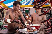 Two shirtless men cooking, BulgariaTek , Bulgaria, August 2011