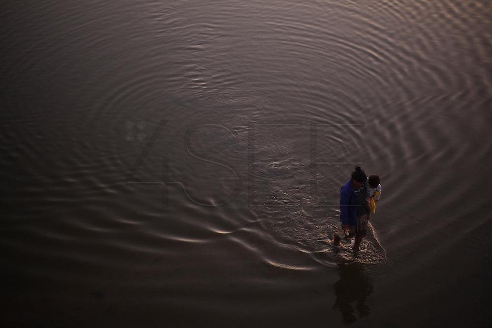 Women crosses the river with a child, Amarapura, Burma.<br /> Note: These images are not distributed or sold in Portugal