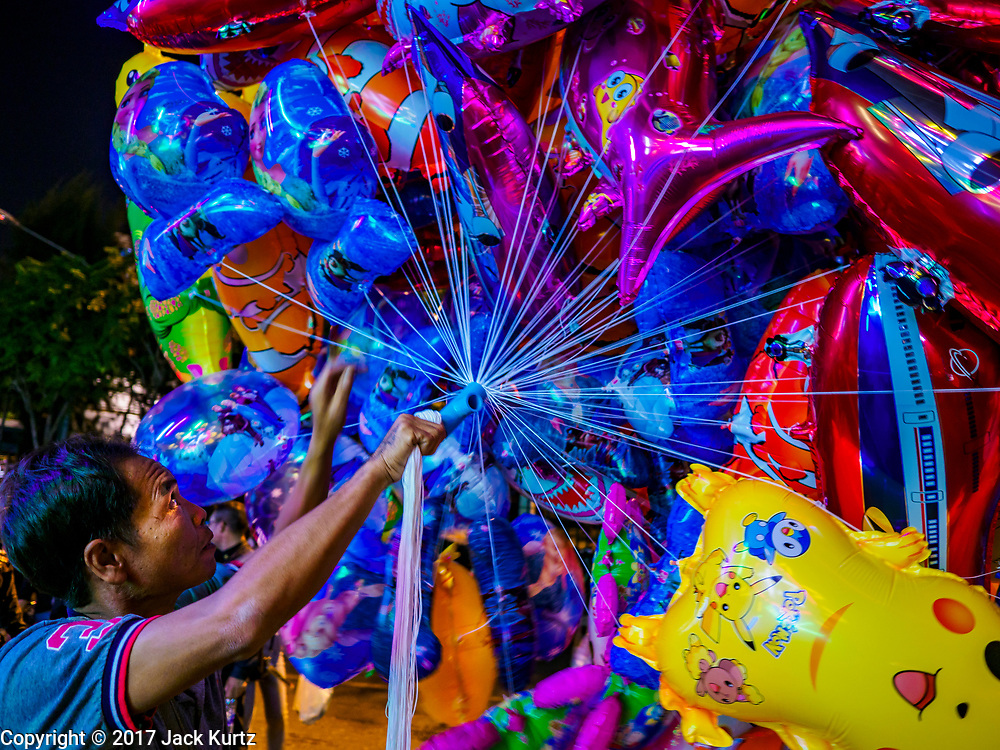 "03 NOVEMBER 2017 - BANGKOK, THAILAND: A vendor sells inflatable toys during Loi Krathong at Wat Prayurawongsawat on the Thonburi side of the Chao Phraya River. Loi Krathong is translated as ""to float (Loi) a basket (Krathong)"", and comes from the tradition of making krathong or buoyant, decorated baskets, which are then floated on a river to make merit. On the night of the full moon of the 12th lunar month (usually November), Thais launch their krathong on a river, canal or a pond, making a wish as they do so. Loi Krathong is also celebrated in other Theravada Buddhist countries like Myanmar, where it is called the Tazaungdaing Festival, and Cambodia, where it is called Bon Om Tuk.     PHOTO BY JACK KURTZ"