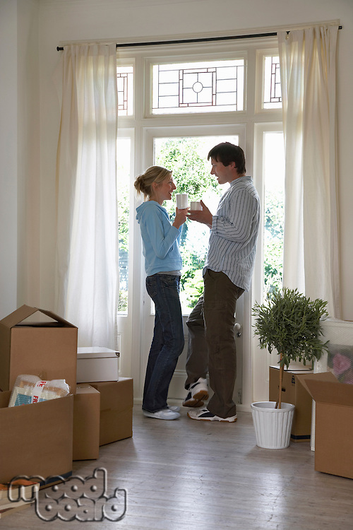Couple standing by window surrounded by boxes