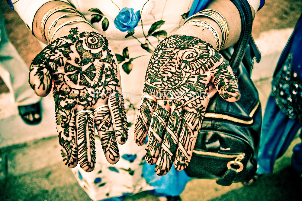 A woman reaches out with her hands with fresh henna tattoo, India.