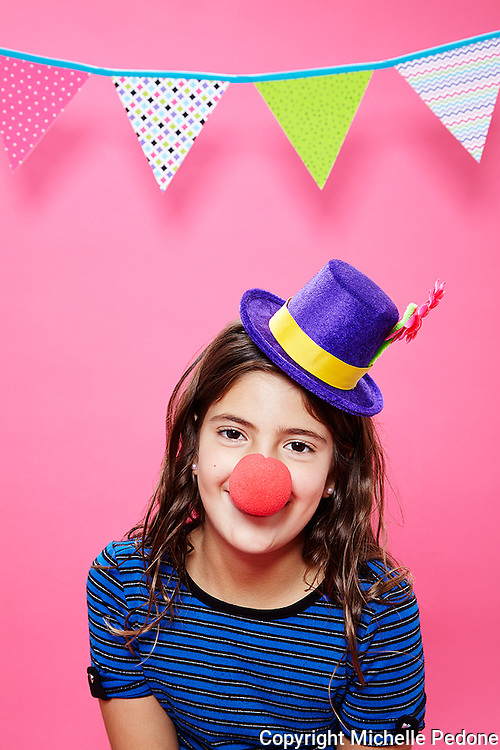 Portrait of Tween girl wearing clown hat and nose against pink background.<br /> Photographed at Photoville Photo Booth September 20, 2015