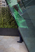 A Man's leg seen at the bottom of corporate office windows, on 14th September 2017, in London, England.