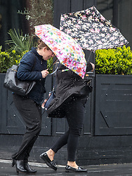 © Licensed to London News Pictures. 12/04/2017. Manchester, UK. Two women in the Spinningfields office district of Manchester battle against bitter winds and icy rain , which inverts umbrellas , during a sudden squall in Manchester City Centre . Photo credit: Joel Goodman/LNP