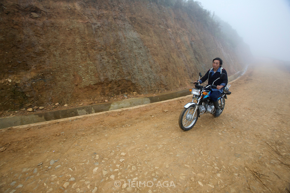 Hilltribe villages around Sapa. Black Hmong on motorbike.