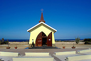 Aruba's Alto Vista chapel sits atop a hill with a stunning view of the surrounding ocean as seen in this August 28, 2005 photo. The bright yellow chapel has indoor and outdoor pews. White crosses, marking the stations of the cross, line the winding road approaching the chapel.