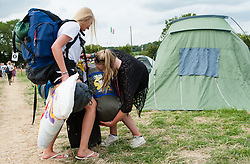 © Licensed to London News Pictures. 24/06/2015. Pilton, UK.   Festival goers arriving at  Glastonbury Festival struggle with their luggage during a warm sunny afternoon on  Wednesday Day 1 of the festival.        The pedestrian gates to the festival opened at 8am this morning, with many festival goers arriving and waiting throughout last night for the opening.  This years headline acts include Kanye West, The Who and Florence and the Machine, the latter having been upgraded in the bill to replace original headline act Foo Fighters.  Photo credit: Richard Isaac/LNP