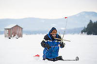 Dan Maloney of Nottingham sets his tip up on Meredith Bay Friday morning in preparation for the Great Meredith Rotary Ice Fishing Derby.  (Karen Bobotas/for the Laconia Daily Sun)