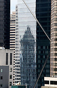 A shimmery reflection of Seattle's original skyscraper, the 38-story Smith Tower, completed in 1914 on Second Avenue in the Pioneer Square neighborhood, is seen in the glass panels of downtown's new, 48-story F5 Tower on Fifth Avenue. (Greg Gilbert / The Seattle Times)