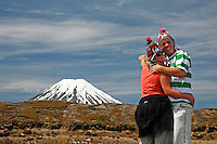 Happy couple laughing with the famous Mt Ngarahoe Mt Doom in the back drop at Tongariro national Park New Zealand