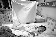 China's Aging Population 8 - An attendent puts a sheet over a comatose woman a Beijing hospice for the elderly.
