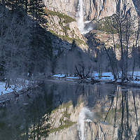 Yosemite Falls reflecting in the still waters of Merced River. Yosemite National Park, California