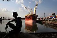 A labourer rests during his break as ships unload cargo at the Netaji Subash Chandra Docks in Kolkatta,  India, on Monday, June 6, 2011.  Photographer: Prashanth Vishwanathan/Bloomberg News
