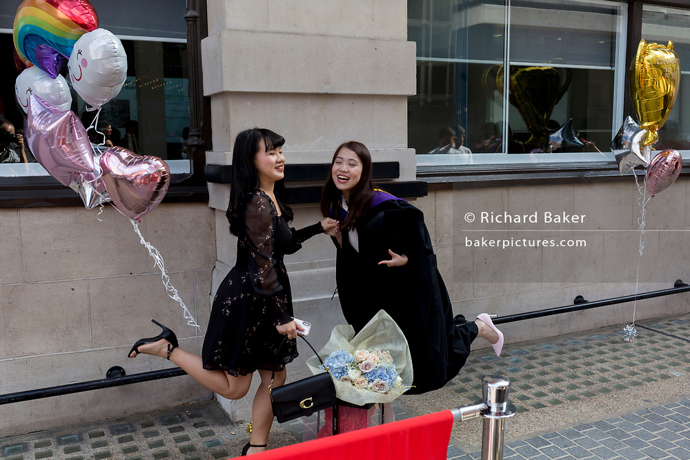 Friends and family of Hillary Chung (right), a 21 year-old Law graduate from Hong Kong, celebrate her graduation with a 2:1 degree outside the London School of Economics (LSE) after her graduation ceremony, on 22nd July 2019, in London, England.