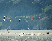 Kite boarders stand on an sand bar near Squamish Terminals.  An extra low tide exposed the normally submerged sand bar.  Saturday, May 27, 2017.  Photo by David Buzzard/For The Squamish Chief.