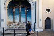 A couple admire a depiction of the crucifixion outside the Church of the Visitation of the Blessed Virgin Mary on Karmelicka street in the city of krakow, on 22nd September 2019, in Krakow, Malopolska, Poland.
