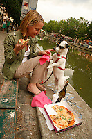 A woman and her dog share a pizza, canal st martin, paris