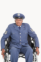 Portrait of a disabled senior male US Air Force officer in wheelchair over gray background