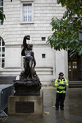 © Licensed to London News Pictures . 30/09/2017. Manchester, UK. Police investigate a statue opposite the Midland Hotel with an anti-austerity poster pasted to its chest as Manchester prepares for the Conservative Party Conference , which is taking place inside a secured zone around the Manchester Central Convention Centre . Photo credit: Joel Goodman/LNP
