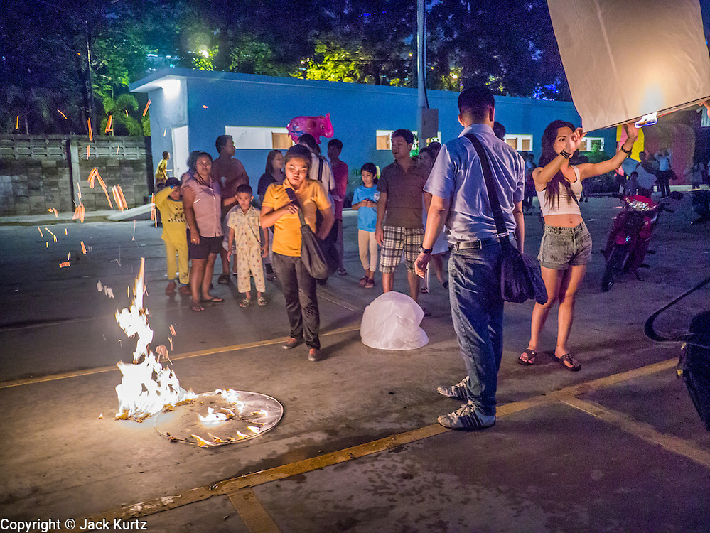 28 NOVEMBER 2012 - BANGKOK, THAILAND:  A Khom Loi lantern burns on the ground after it floated up a few feet and then crashed back to earth while people try to light another Khom Loi lantern  during Loy Krathong at Wat Yannawa in Bangkok. The lanterns are a part of the Loy Krathong tradition in northern Thailand, and are becoming popular in Bangkok. But authorities don't allow their use in Bangkok because of the fire danger. They try to stop people from launching the lanterns in Bangkok. Loy Krathong takes place on the evening of the full moon of the 12th month in the traditional Thai lunar calendar. In the western calendar this usually falls in November. Loy means 'to float', while krathong refers to the usually lotus-shaped container which floats on the water. Traditional krathongs are made of the layers of the trunk of a banana tree or a spider lily plant. Now, many people use krathongs of baked bread which disintegrate in the water and feed the fish. A krathong is decorated with elaborately folded banana leaves, incense sticks, and a candle. A small coin is sometimes included as an offering to the river spirits. On the night of the full moon, Thais launch their krathong on a river, canal or a pond, making a wish as they do so.   PHOTO BY JACK KURTZ
