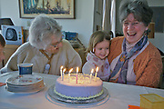 Grandmother and elderly Aunt, also celebrating her birthday, encourage child to blow out the candles on the cake