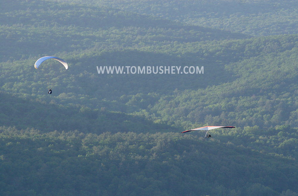 Ellenville, NY - A hang glider and a paraglider soar over a forest on May 30, 2009.